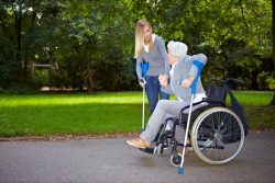 caregiver assisting an old woman in a wheelchair