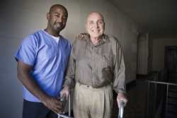 caregiver assisting an old man to walk