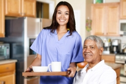 caregiver serving a breakfast to an old man