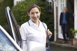 a portrait of a caregiver smiling in front of a car