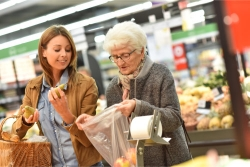 caregiver assisting an elderly woman in grocery shopping