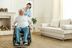 caregiver assisting an old man in a wheelchair