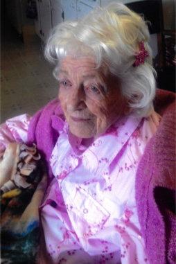 old white haired lady wearing a pink shirt with a dark pink bow