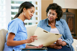 caregiver showing document to elderly woman